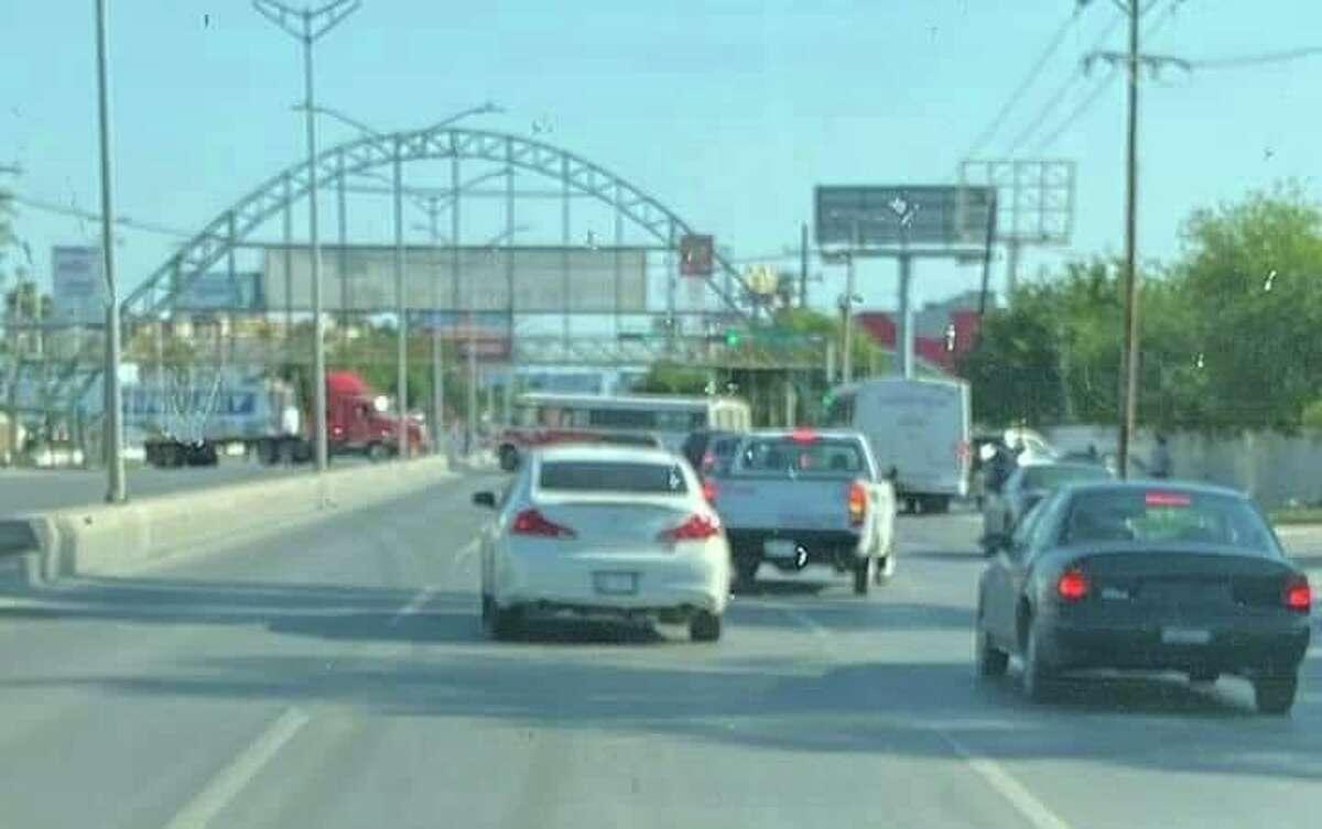 Un camión urbano aparece al fondo de la imagen bloqueando una de las avenidas principales de Nuevo Laredo, México, el miércoles, durante una serie de acciones como represalia por la muerte de un alto líder del cártel CDN en un enfrentamiento con las autoridades.