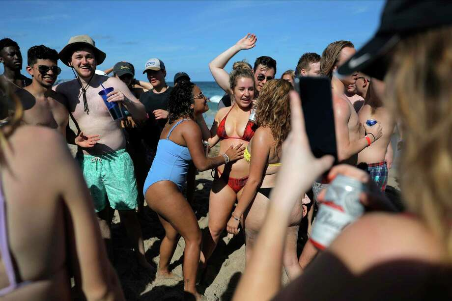 College age spring break students party on the beach, Tuesday, March 17, 2020, in Pompano Beach, Fla. As a response to the coronavirus pandemic, Florida Gov. Ron DeSantis ordered all bars be shut down for 30 days beginning at 5 p.m. and many Florida beaches are turning away spring break crowds urging them to engage in social distancing. (AP Photo/Julio Cortez) Photo: Julio Cortez, STF / Associated Press / Copyright 2020 The Associated Press. All rights reserved.