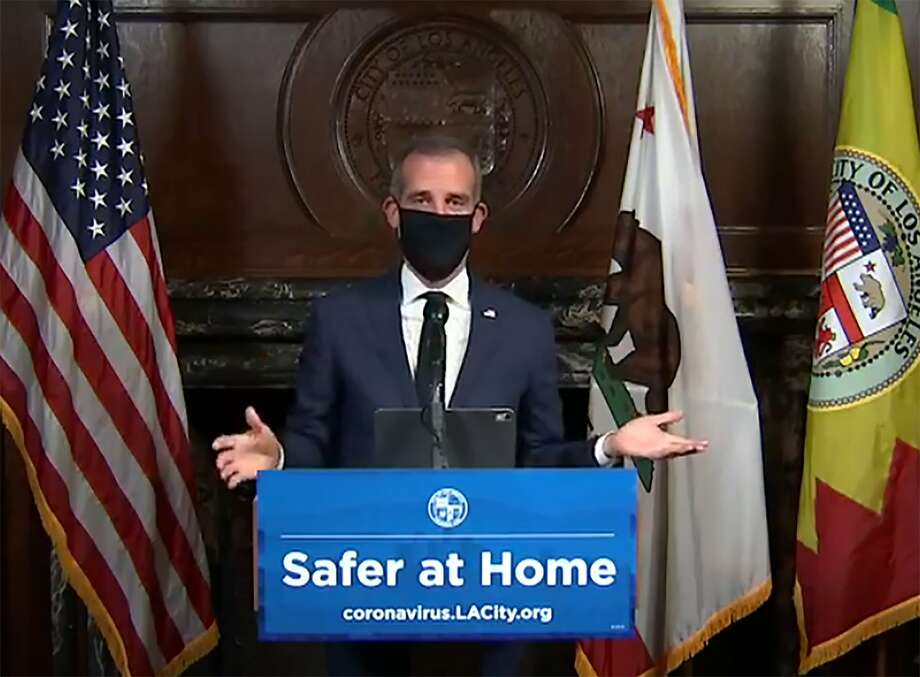 This still image taken from a live stream provided by Office of Mayor Eric Garcetti shows Los Angeles Mayor Garcetti displaying putting on a protective face mask during his daily news conference in Los Angeles on Wednesday, April 1, 2020. or Eric Garcetti via AP) Photo: Associated Press