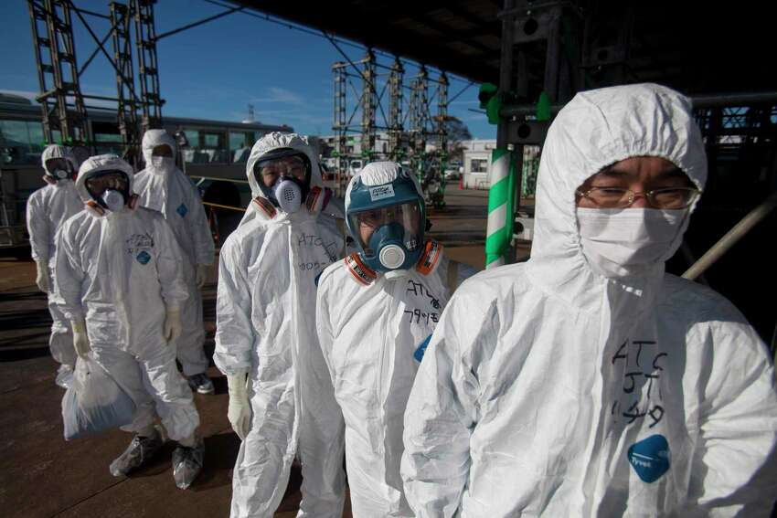 FILE - This Nov. 12, 2011, file photo, shows workers in protective suits and masks as they wait to enter the emergency operation center at the crippled Fukushima Dai-ichi nuclear power station in Okuma, Japan. The shortage of protective gear caused by the coronavirus pandemic has hit the workers at the meltdown-hit Fukushima nuclear plant in Japan, where they've needed them daily for years to guard against radiation. Shipments temporarily stopped coming in, although an alternative supplier was later found, according to Tokyo Electric Power Co., the utility that runs Fukushima Dai-ichi.