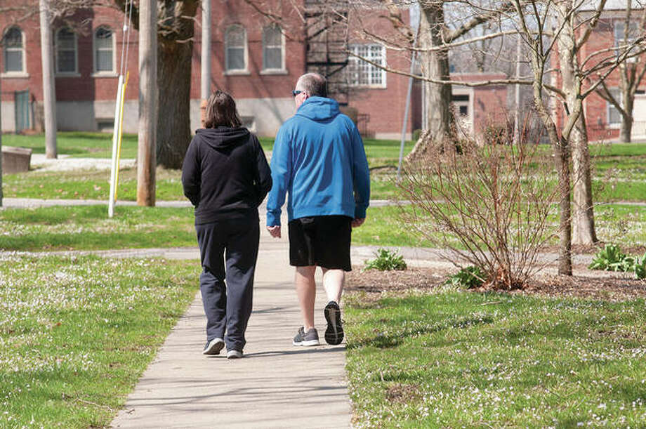 "Marylou and Rodger Heaton walk Wednesday on West State Street. Rodger Heaton said being outside ""breaks up the monotony from staying home and doing puzzles"" while following the state's stay-at-home order. Photo: Darren Iozia 