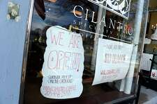 Cilantro Specialty Foods advertises online ordering on the front window of their Guilford food store and cafe on March 21, 2020.