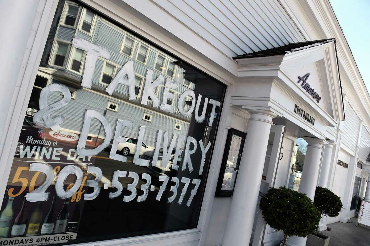 Amarone Restaurant on Water Street in Guilford advertises their takeout and delivery options on their front window on March 21, 2020.