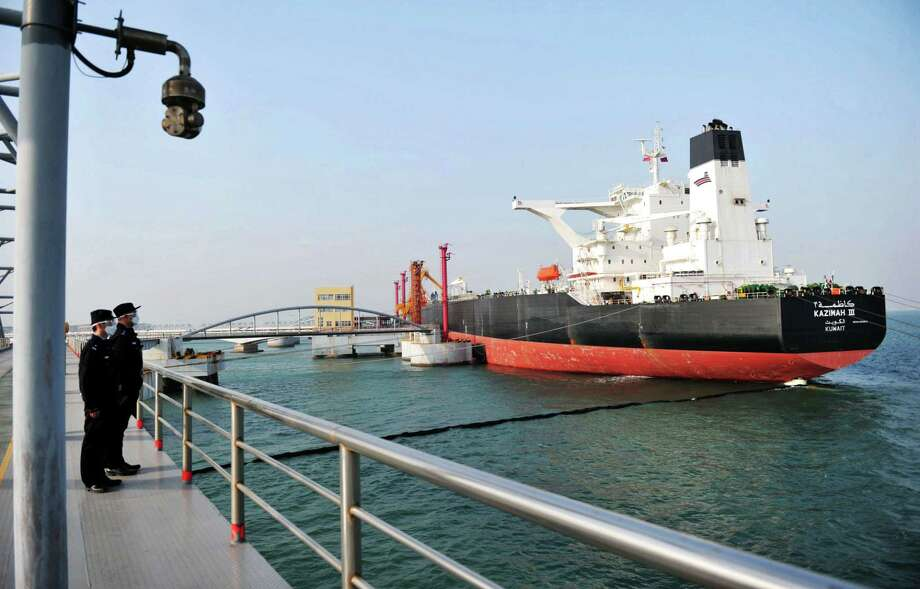 Police watch as a Kuwaiti oil tanker unloads crude oil at the port in Qingdao, in China's eastern Shandong province. Photo: STR, AFP Via Getty Images / AFP or licensors