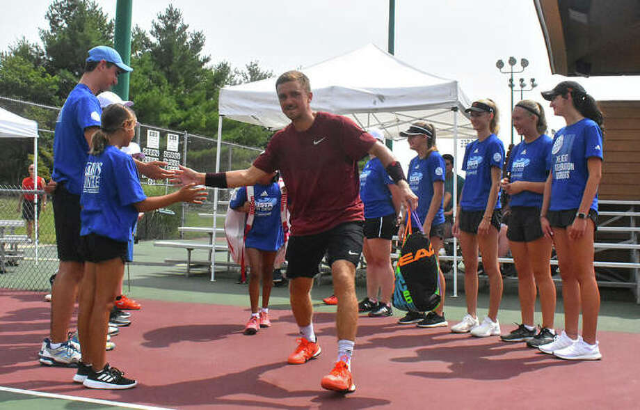 Nathan Ponwith is welcomed by the ball kids before the start of his Edwardsville Futures singles championship match last year.