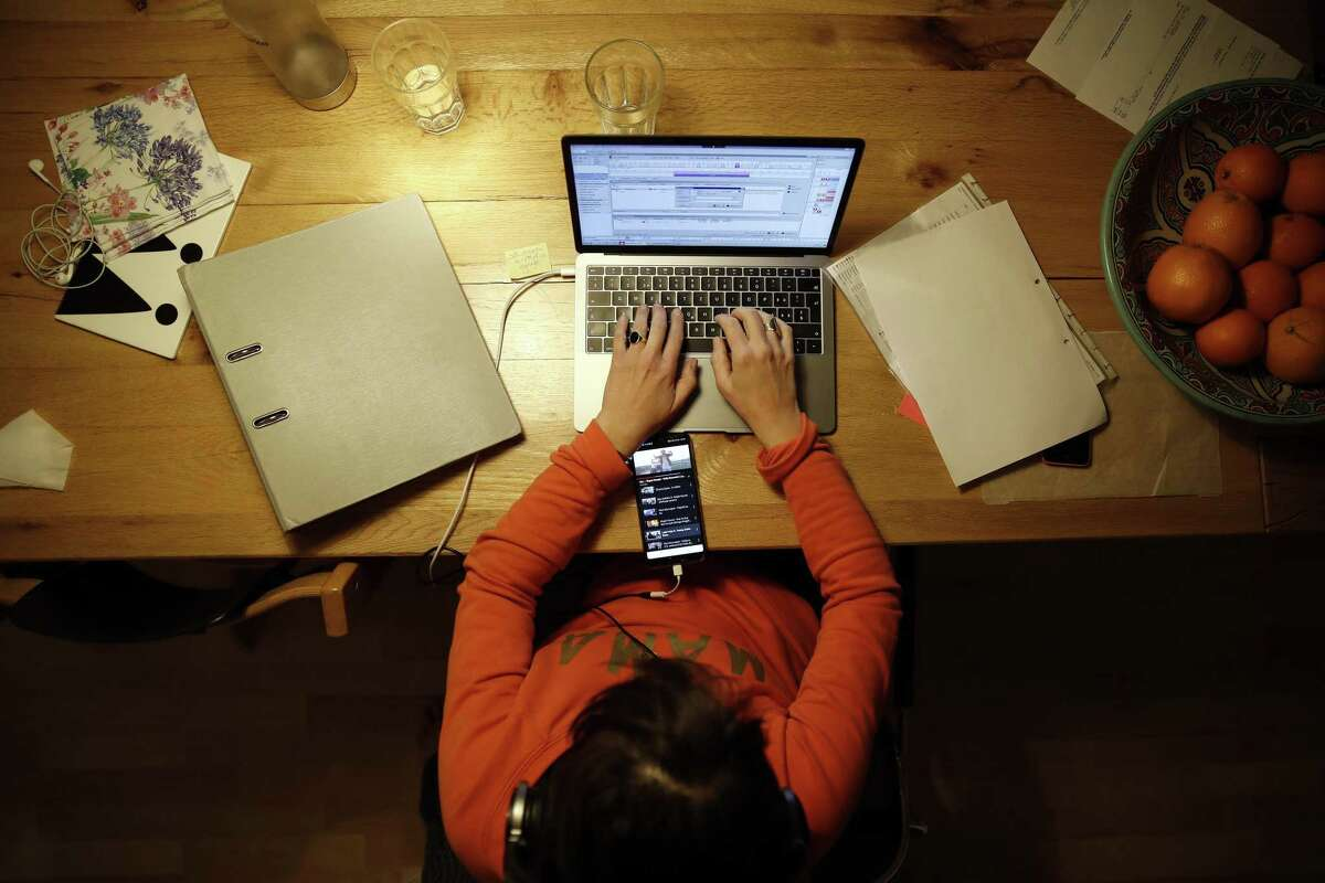 A woman works at a laptop computer at home in an arranged photograph taken in Bern, Switzerland, on Wednesday, April 1, 2020. The Covid-19 pandemic has triggered a seismic wave of health awareness and anxiety, which is energizing a new category of virus-fighting tech and apps. Photographer: Stefan Wermuth/Bloomberg