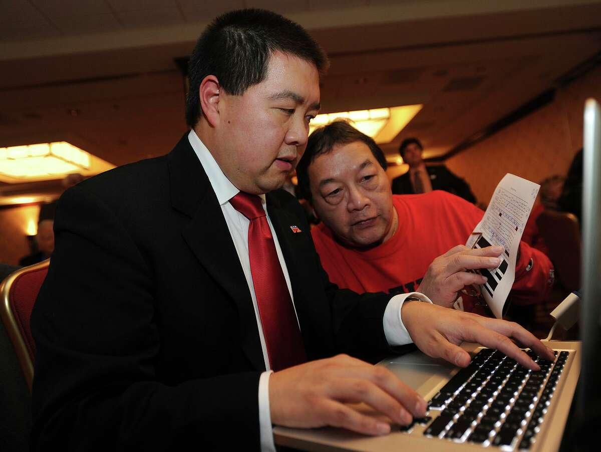 Bill Chin, left, and his father Ken Chin, both of Trumbull, post election results at the Trumbull Marriott in Trumbull, Conn. on Tuesday, November 4, 2014.