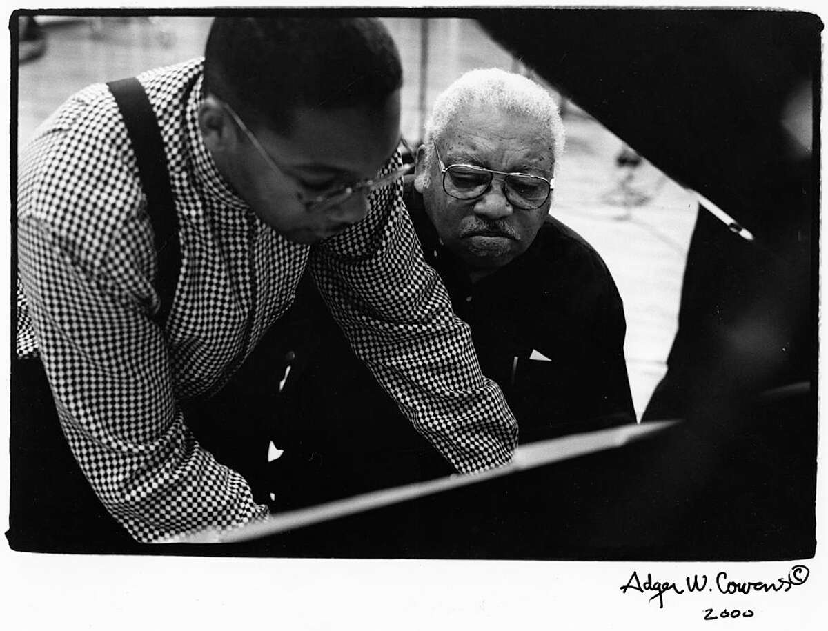 Ameican jazz musician jazz pianist Ellis Marsalis Jr (right) watches as his son, fellow jazz musician Wynton Marsalis leans over his shoulder to play piano, New York, New York, 1990s. (Photo by Adger Cowans/Getty Images)