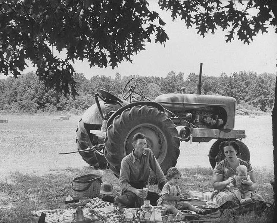 A picnic lunch provides a pleasant break for Charlie Eater and family, who raises dairy cattle on the 40 acres he owns, and another 250 acres he rents. Photo: Howard Sochurek | The Life Picture Collection (Getty Images)