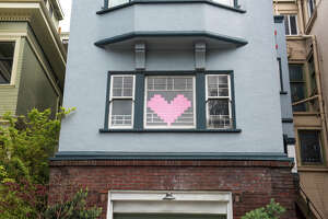 A heart made up of pink Post-it notes is displayed in a home window on Van Ness Ave., Tuesday, March 31, 2020.