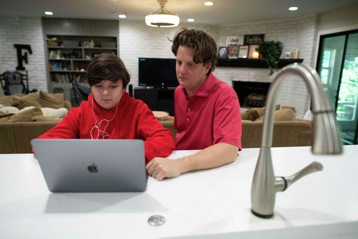 Chris Funk works with his son, Ezra, during homeschool. The Funk family has been homeschooling for five years.