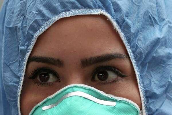 Una enfermera, vestida con ropa protectora como medida de precaución contra el nuevo coronavirus, espera mientras revisa la temperatura de los viajeros en un puesto de control afuera de una estación de autobuses en Soacha, en las afueras de Bogotá, Colombia, el miércoles 1 de abril de 2020. (AP Foto/Fernando Vergara)