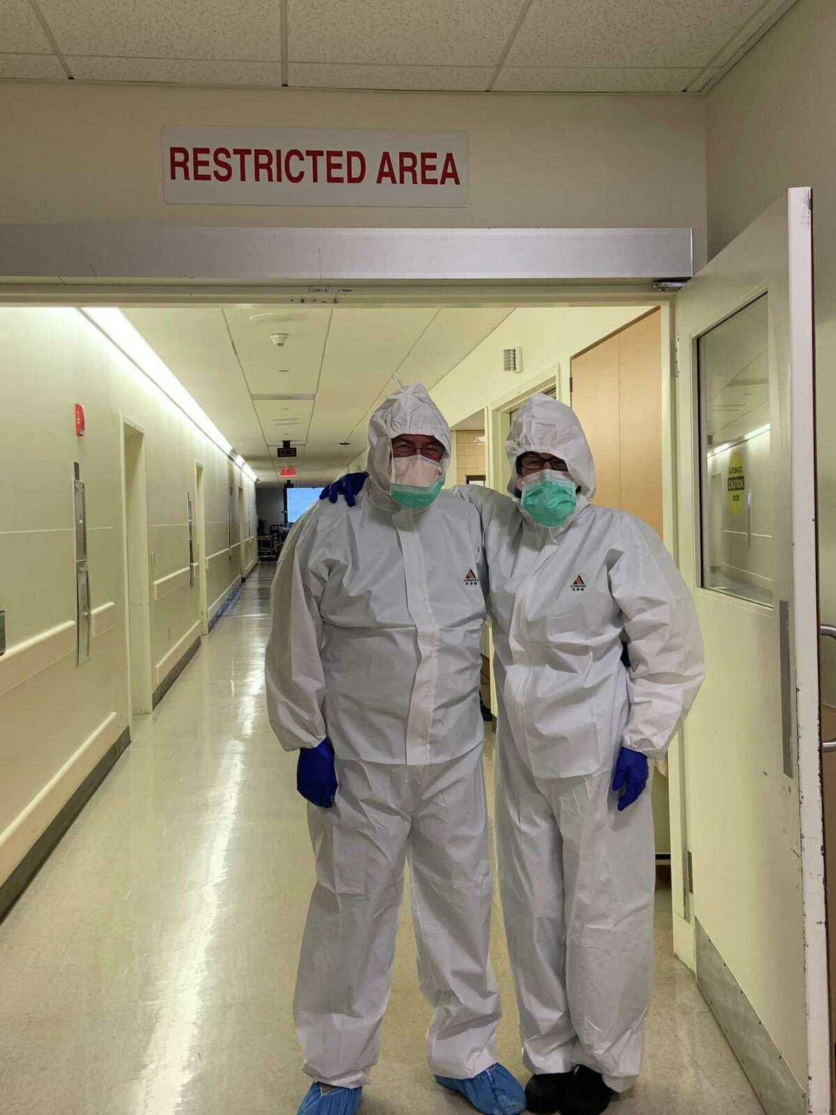 Paul Darragh, CRNA and Theresa Bowling, MD, at St. Vincent's Medical Center, Bridgeport in coveralls from Grace Farms Foundation.