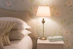 Illuminated bedside light on a table with tissue box and part of bed in view. Soft muted colours in a calm setting.
