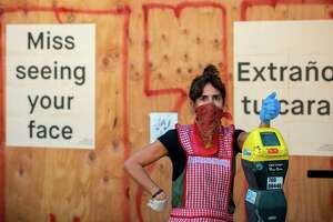 Restaurant owner Lorena Zeruche looks on wearing a bandana on her face as she prepares for take-out only in San Francisco, California on April, 1, 2020, during the novel coronavirus outbreak.