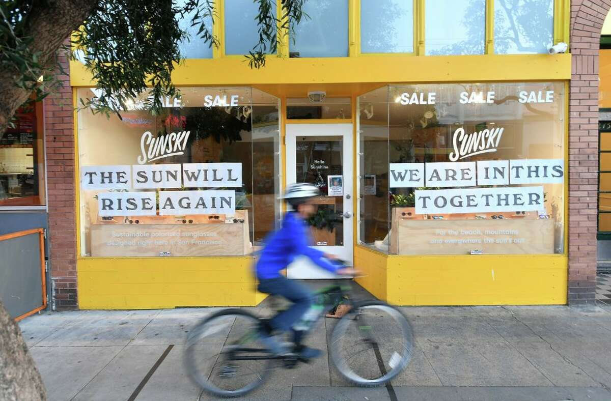 A boy rides his bike passed a supportive sign posted on a storefront in San Francisco, California on April, 1, 2020,