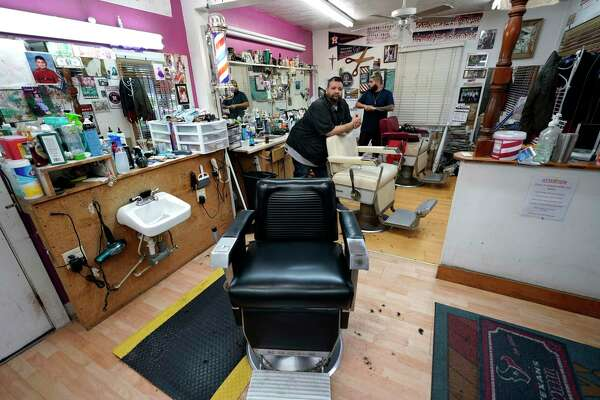 Carlos Vasquez, left, and his nephew, R.J. Vasquez, wait for customers at their family's barber shop in Houston. They estimate they have lost nearly half of their business due to the COVID-19 coronavirus.