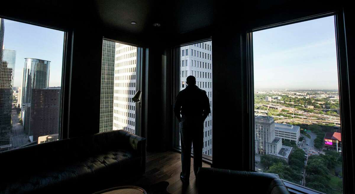 Lee McKelvey, a pipeline control room operator at EVX Midstream, looks out a 25th floor window from an empty office as he takes a break on Wednesday, April 1, 2020 in Houston. With tens of thousands of people working from home due to the conronavirus outbreak, downtown Houston has become a ghost town except for a handful of energy company control room operators, security guards and janitors in the buildings and construction workers in the streets.