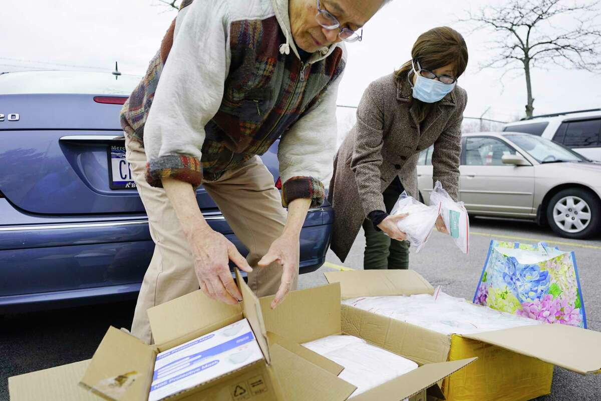 Chibao Miaw, left, and his wife, Lilly Miaw, go through face masks and other protective gear outside of UPS after picking up the shipment of boxes on Thursday, April 2, 2020, in Latham, N.Y. Chinese community members have been organizing shipments of the supplies from China to distribute to area hospitals. Many of the masks have been donated by Chinese community members or their relatives in China. The local community has also raised $35,000 to purchase more protective equipment in China and to have it shipped over. (Paul Buckowski/Times Union)