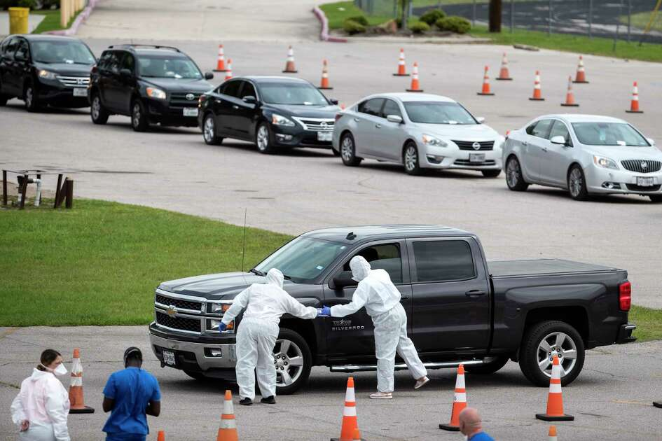 People are screened as they line up to be tested for coronavirus at a free testing site at Forest Brook Middle School set up by United Memorial Medical Center on Thursday, April 2, 2020 in Houston.