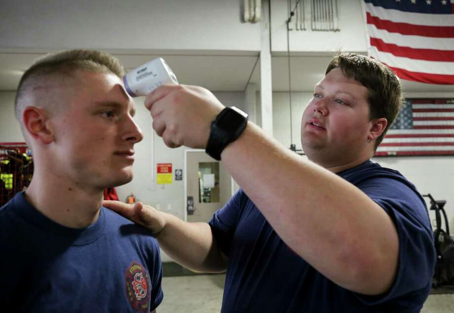 Matthew Bayes, right, takes the temperature of fellow firefighter Braxton Cole at the start of their shift at the Stafford Fire Department Station 1 on Tuesday, March 24, 2020, in Stafford, Texas. The step has been added as a precaution to the spread of the COVID-19 pandemic. Photo: Godofredo A. Vásquez, Houston Chronicle / Staff Photographer / © 2020 Houston Chronicle