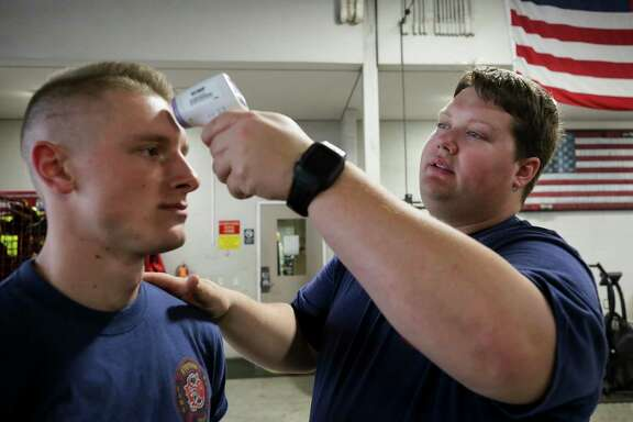 Matthew Bayes, right, takes the temperature of fellow firefighter Braxton Cole at the start of their shift at the Stafford Fire Department Station 1 on Tuesday, March 24, 2020, in Stafford, Texas. The step has been added as a precaution to the spread of the COVID-19 pandemic.