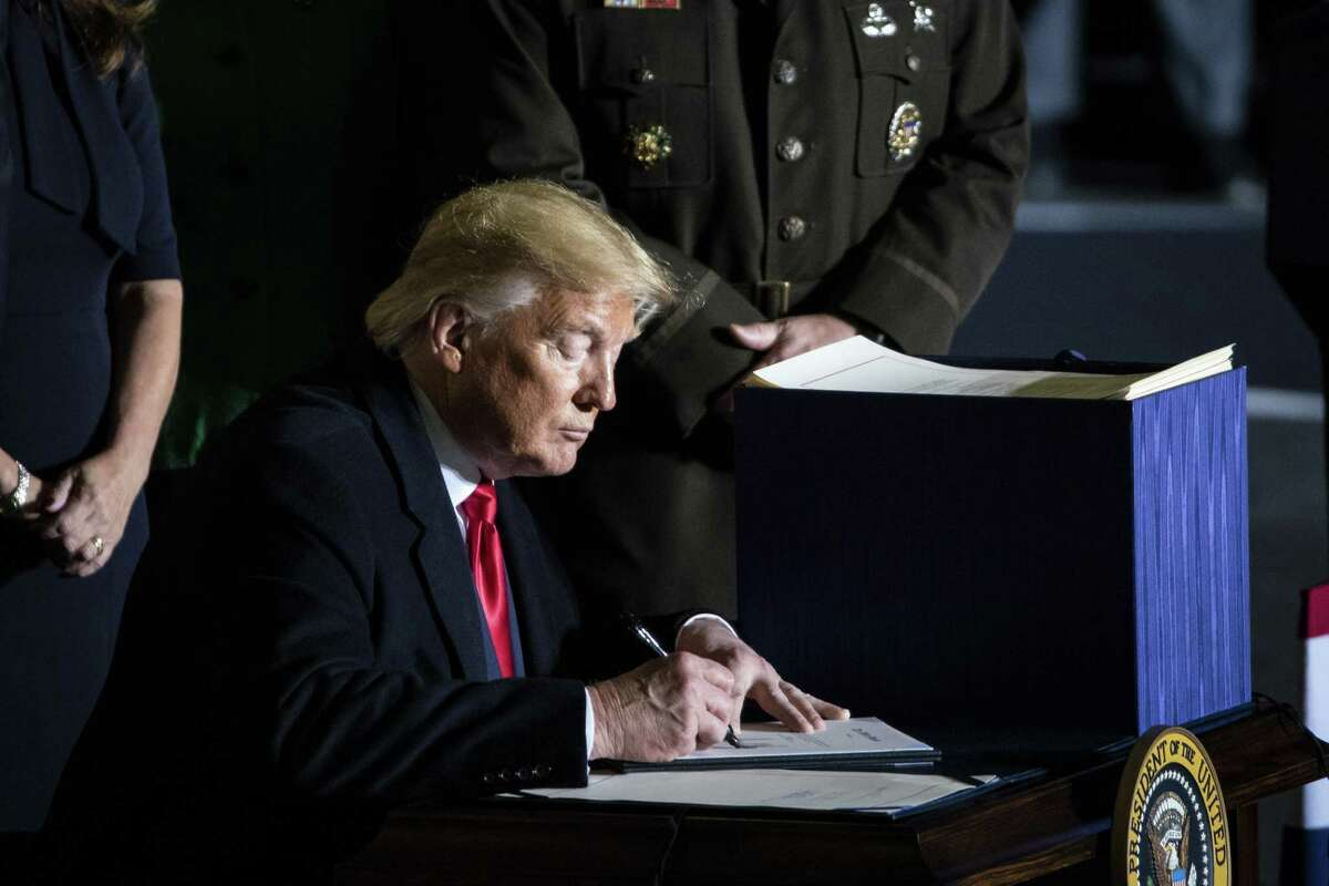 U.S. President Donald Trump signs the National Defense Authorization Act for Fiscal Year 2020 during a ceremony at Joint Base Andrews, Maryland, U.S., on Friday, Dec. 20, 2019. Photographer: Al Drago/Bloomberg