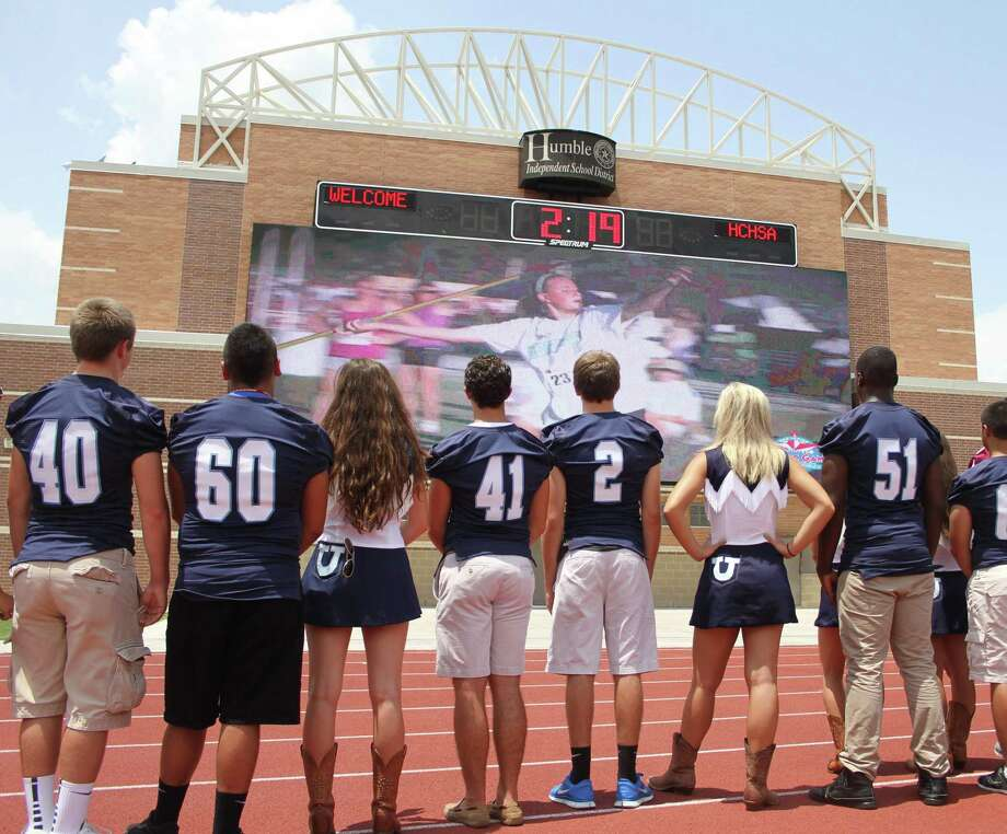 Students from Kingwood High School watch the unveiling of a new video board at George Turner Stadium for the upcoming AAU Junior Olympic Games on June 12. The 960 square foot video board is the largest at a high school facility in the United States, and will allow Humble ISD to stream game and athlete statistics, live video, instant replays and advertisements simultaneously. In addition to the new screen, Turner Stadium will also have awnings build over the stands and a new road will be built to lessen traffic in and out of the stadium. Photo: Jason Fochtman / HCN / HCN