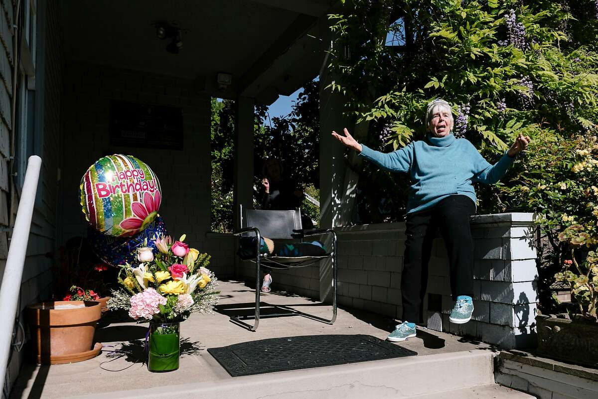 Zona Roberts holds court from her front porch as friends and neighbors gather to celebrate her 100th birthday, in Berkeley, Calif, on Wednesday, April , 2020.