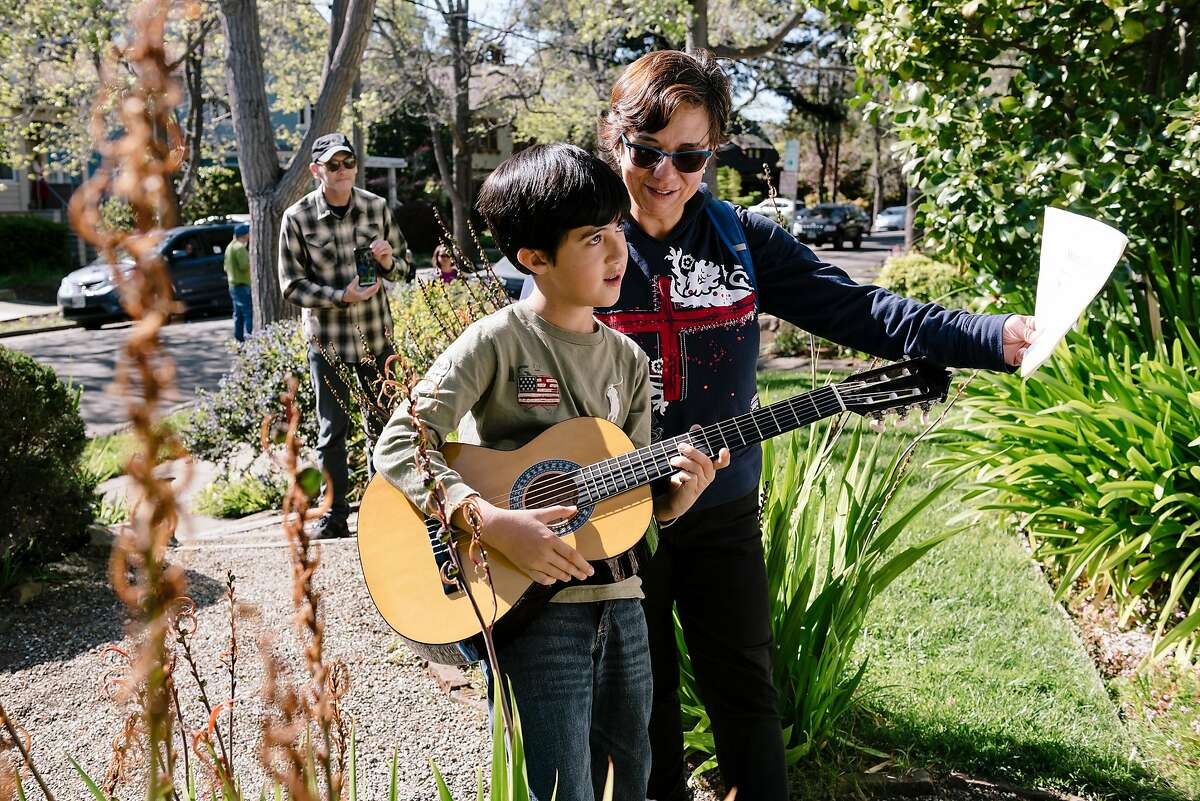 Patricia Riestra holds out sheet music for her son Mateo Aranguren as he plays