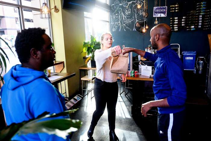 Sarah Holt-Gosselin hands an order to a delivery driver at alaMar on Friday, March 27, 2020, in Oakland, Calif. The restaurant has seen business increase as customers seek take-out and delivery options under coronavirus stay-at-home orders.