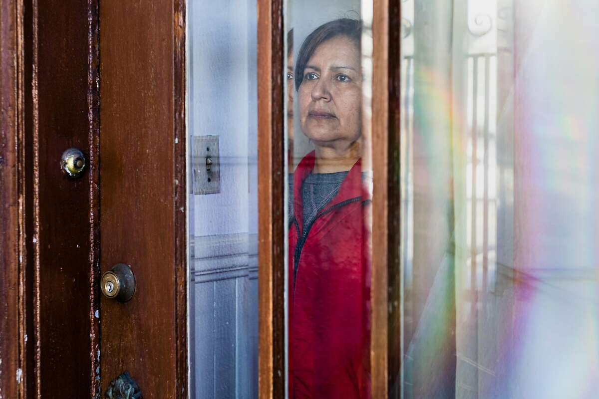 Elena Duran looks out of a door with window in her home on Wednesday, April 1, 2020, in San Francisco, Calif. She and her family lost their jobs two weeks ago due to the economic disaster caused by the coronavirus.