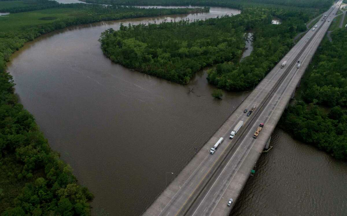 Motorists make their way east and west on Interstate 10 Highway at the Sabine River, which divides Texas and Louisiana. Less traffic means less gasoline and more trouble for the oil industry.
