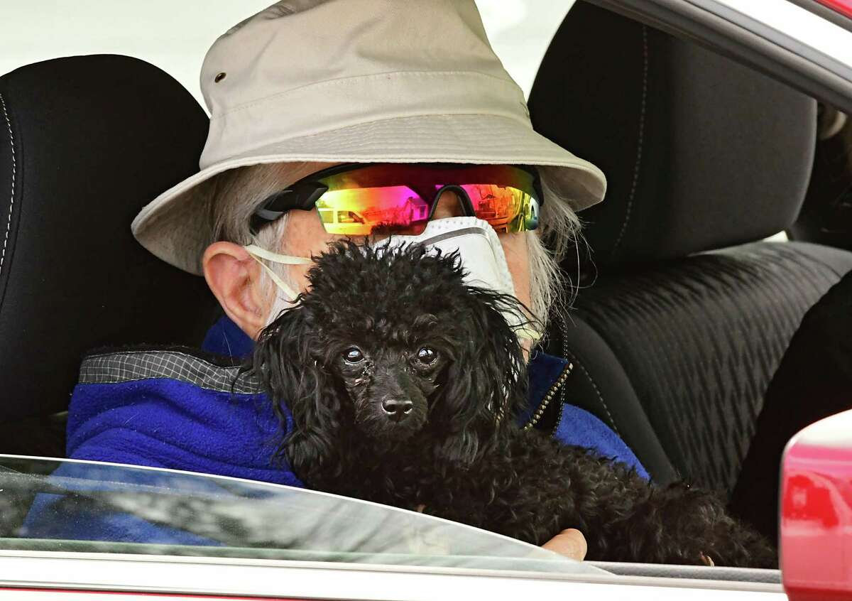 Wayne Wilson of Saratoga Springs holds his Tea Cup Poodle Mena-oo in the waiting room which is in his car outside Saratoga Springs Veterinary Hospital on Thursday April 2, 2020 in Saratoga Springs, N.Y. The animal hospital set up a fenced in fresh air veterinary care examining room outside their building and had the animal's human stay inside their car.(Lori Van Buren/Times Union)