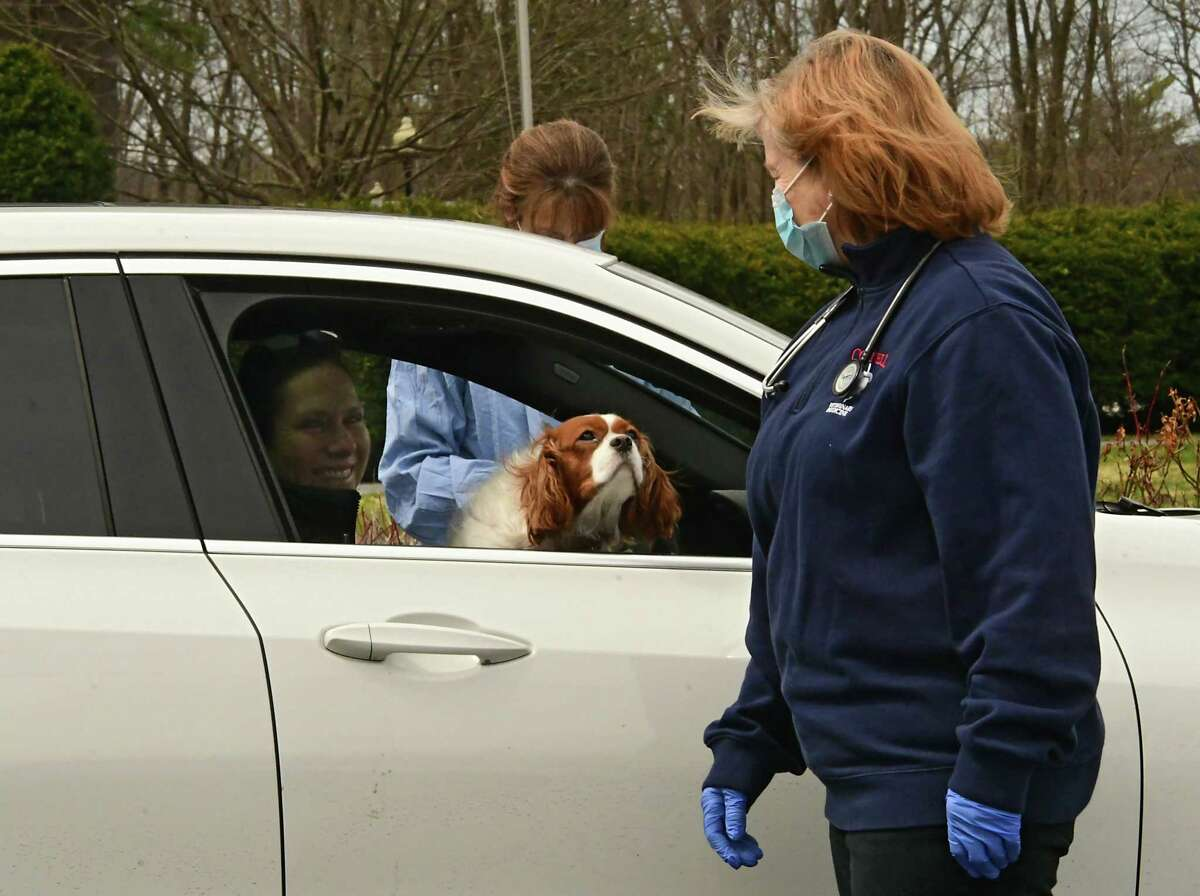 Veterinarian Assistant Tracy Powell, outside driver's side, and Dr. Pamela Reppert talk to Alia Sahlborg in her car outside Saratoga Springs Veterinary Hospital on Thursday April 2, 2020 in Saratoga Springs, N.Y. Sahlborg brought her Cavalier King Charles Spaniel Lucy in for a routine check-up. The animal hospital set up a fenced in fresh air veterinary care examining room outside their building and had the animal's human stay inside their car. (Lori Van Buren/Times Union)