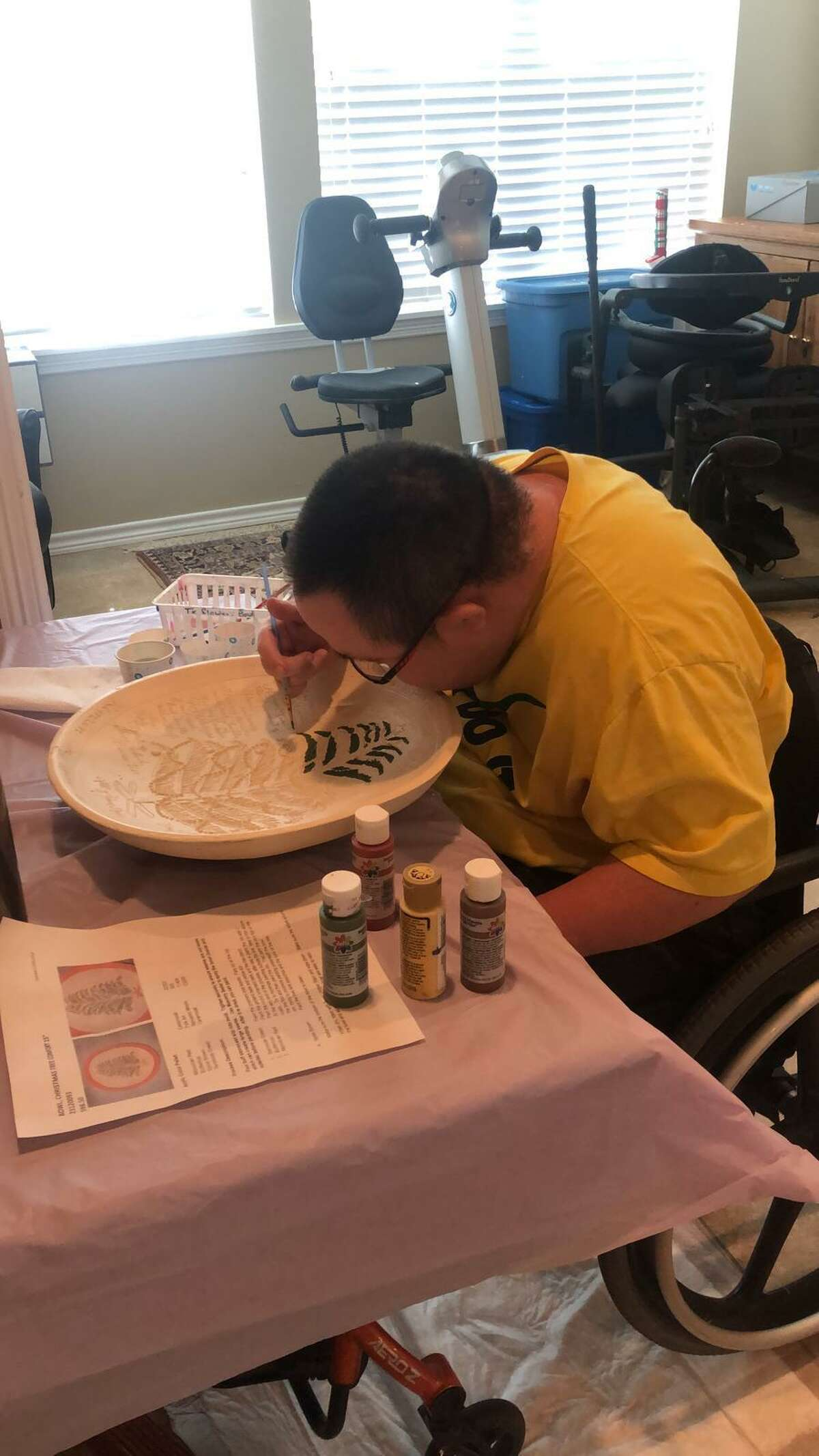 A Brookwood Community citizen paints a bowl from his room. As most of Brookwood's citizens are medically fragile, the community has had to isolate its citizens and alter its programs.