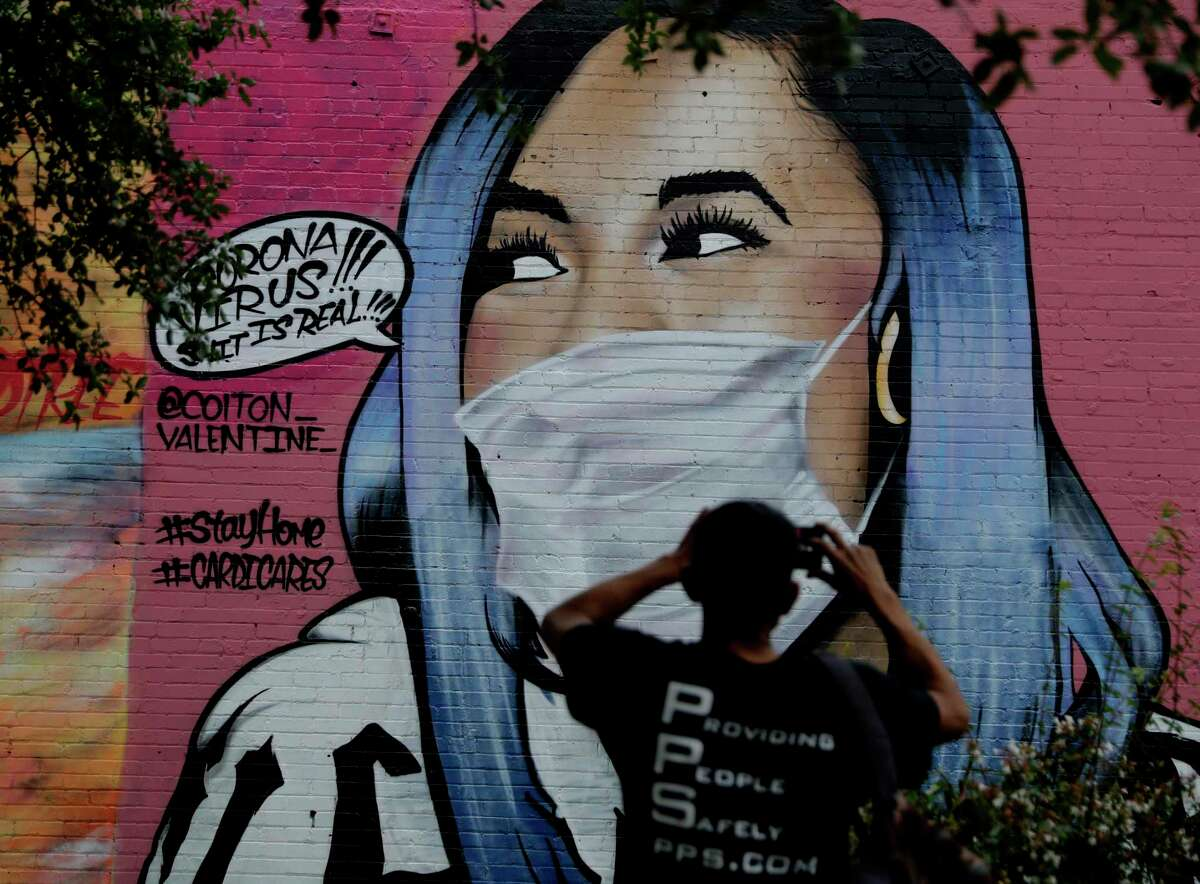 A man photographs a mural of Cardi B that was updated by the artist Colton Valentine to include a face mask to reflect the coronavirus pandemic, in San Antonio, Monday, March 30, 2020. Due to the COVID-19 outbreak, San Antonio an many other Texas cities are under stay-at-home orders. (AP Photo/Eric Gay)