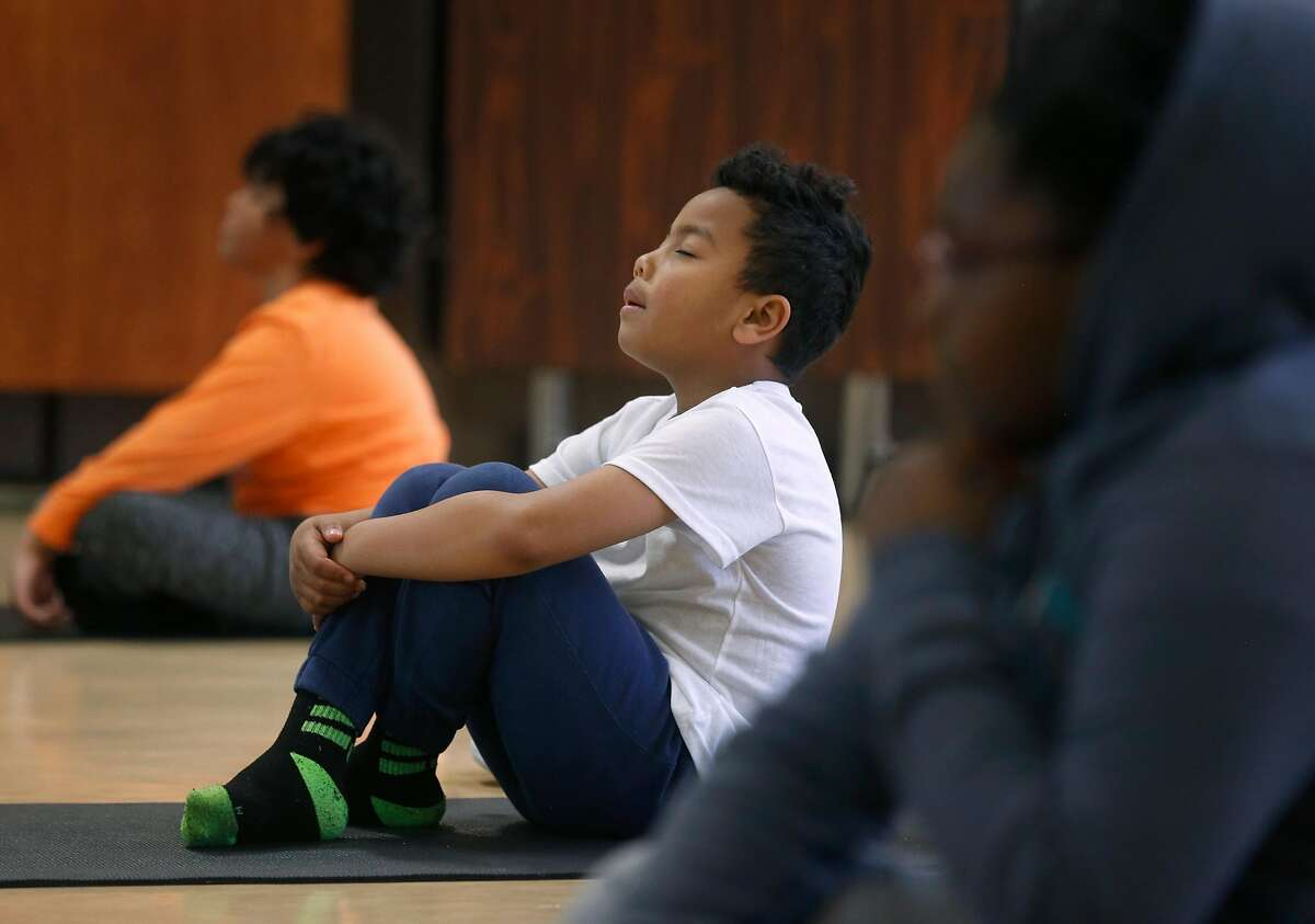 Brandon Franklin meditates in a yoga class during the Pop Up YKids day care program for children of first responders and medical workers at the Mission YMCA in San Francisco, Calif. on Thursday, April 2, 2020.