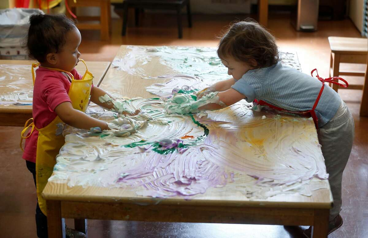 Kalea Johnson (left) and Willow Wilder swirls shaving cream mixed with water colors in an arts and crafts class during the Pop Up YKids day care program for children of first responders and medical workers at the Mission YMCA in San Francisco, Calif. on Thursday, April 2, 2020.