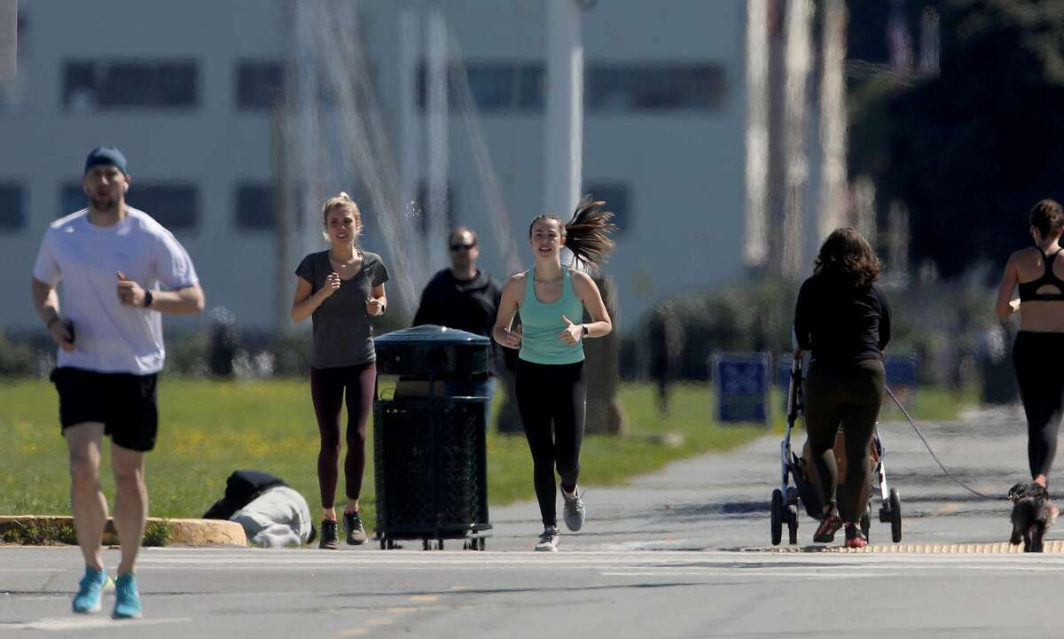 Isabel Glen (middle, green tank)) takes her sister Charlotte Glen (middle left) running at Fort Mason during lunchtime on Thursday, April 2, 2020, in San Francisco, Calif.
