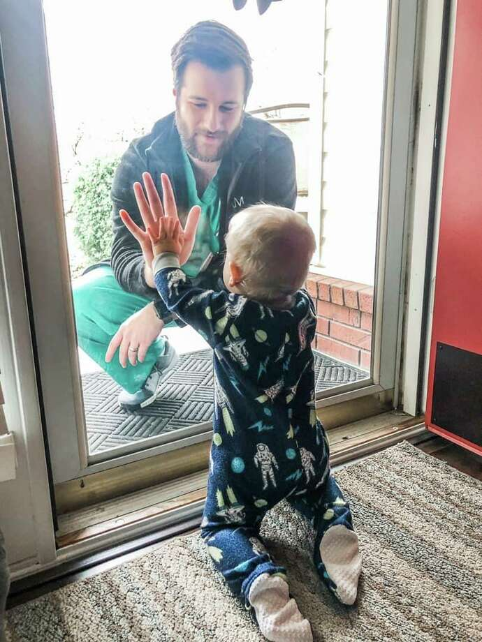 In this March photo from Arkansas, a dad, who is also a doctor, sees his 1-year-old son crawl for the first time, as he touches a glass door between them. A reader says COVID-19 is reminding us all what's most important — family. Photo: /Associated Press / Burks Family