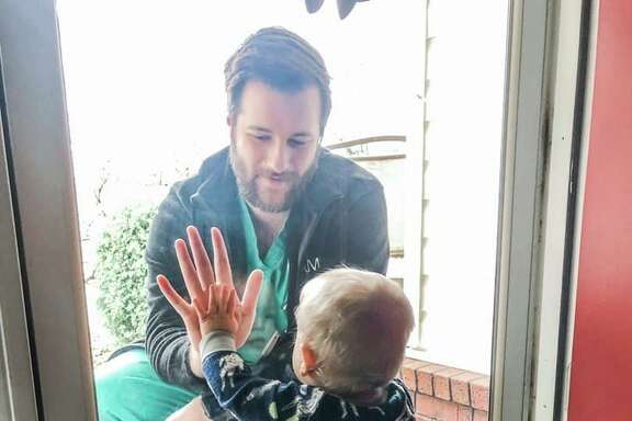 In this March photo from Arkansas, a dad, who is also a doctor, sees his 1-year-old son crawl for the first time, as he touches a glass door between them. A reader says COVID-19 is reminding us all what's most important — family.