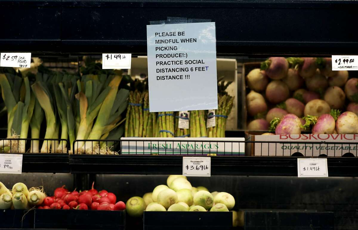 Community Foods Market, located at 3105 San Pablo Ave., encourages customers to practice social distancing and how they pick produce, on Thursday, April 2, 2020, in Oakland, Calif.