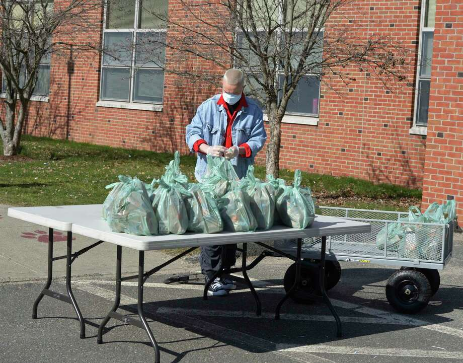 Volunteer Emie Riley helps distribute lunch and breakfast bags at Berry School on Wednesday morning. April 1 2020, in Bethel, Conn. Photo: H John Voorhees III / Hearst Connecticut Media / The News-Times