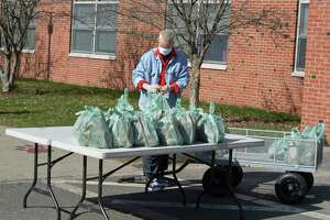 Volunteer Emie Riley helps distribute lunch and breakfast bags at Berry School on Wednesday morning. April 1 2020, in Bethel, Conn.