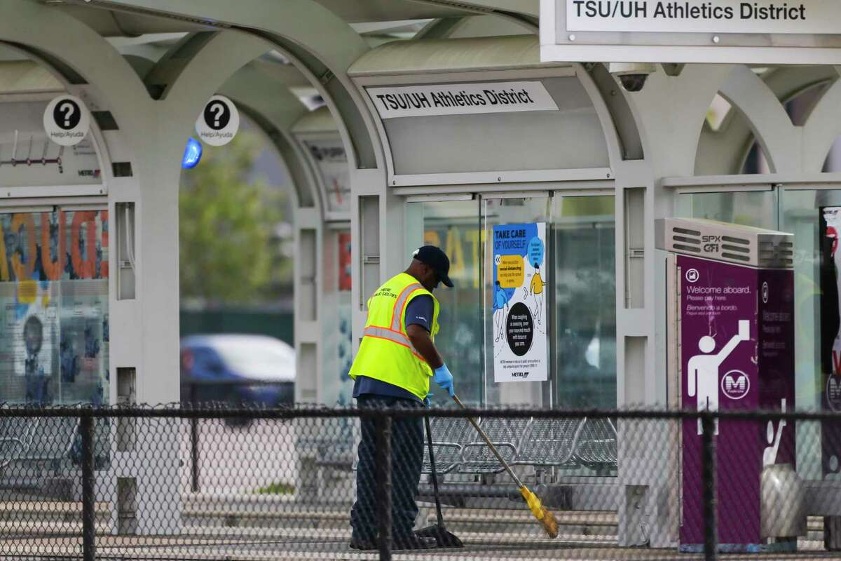 A Metropolitan Transit Authority worker cleans the TSU/UH Athletics District light rail stop on March 26, 2020, near the University of Houston.