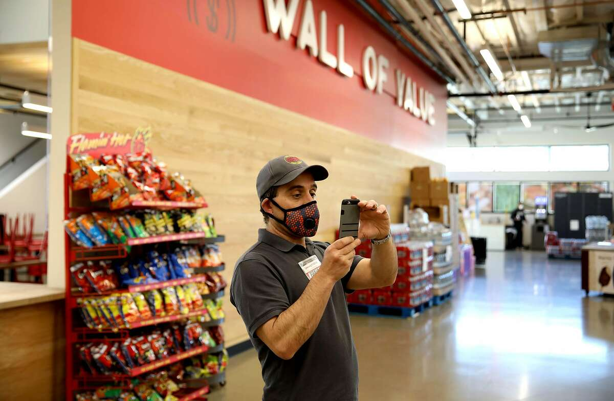Brahm Ahmadi, CEO, snaps images of items that need pricing at Community Foods Market, located at 3105 San Pablo Ave., on Thursday, April 2, 2020, in Oakland, Calif.