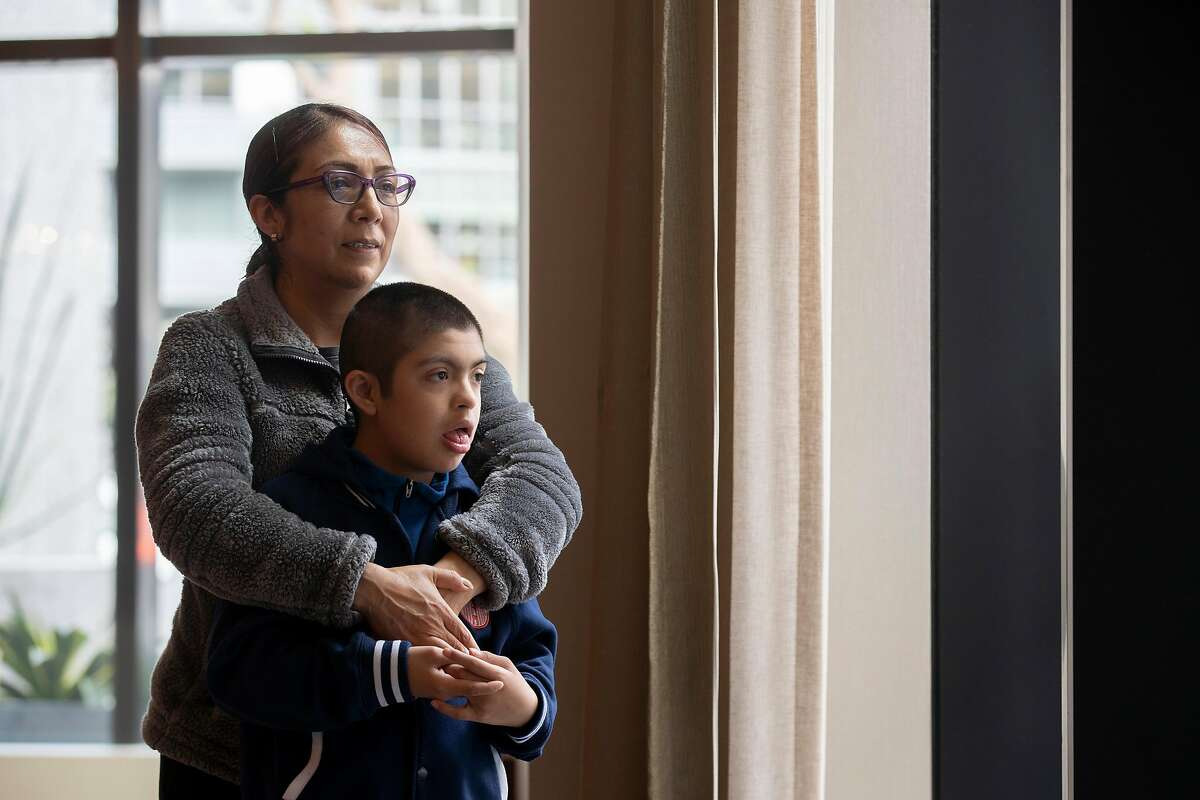 A portrait of Olivia Fraga and her ten-year-old son Martin Perez-Fraga at their apartment�s lobby on Tuesday, March 31, 2020, in San Francisco, Calif. With schools closed because of coronavirus pandemic, Martin is no longer receiving all the services he would get at school. Martin has Down syndrome.