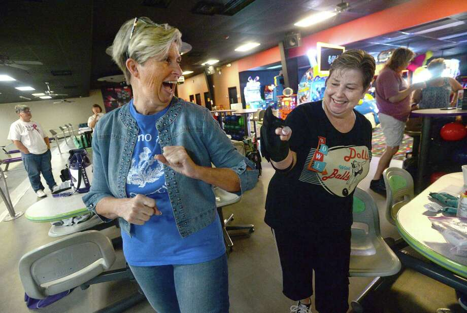 Rebecca Bowden (left) and Jeanne Riley celebrate a strike with an elbow bump as they and other members of the Queen Tumblers League gather at the Max Bowl in Port Arthur for their usual Wednesday morning league games. Photo taken Wednesday, March 18, 2020 Kim Brent/The Enterprise Photo: Kim Brent / The Enterprise / BEN