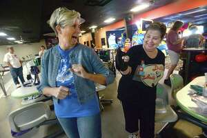 Rebecca Bowden (left) and Jeanne Riley celebrate a strike with an elbow bump as they and other members of the Queen Tumblers League gather at the Max Bowl in Port Arthur for their usual Wednesday morning league games. Photo taken Wednesday, March 18, 2020 Kim Brent/The Enterprise
